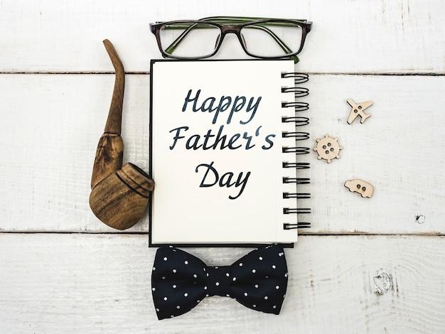 Cahier pour féliciter votre père, lunettes, crayon, stylo sur une belle table blanche. vue de dessus d'un gros plan. préparation pour les vacances