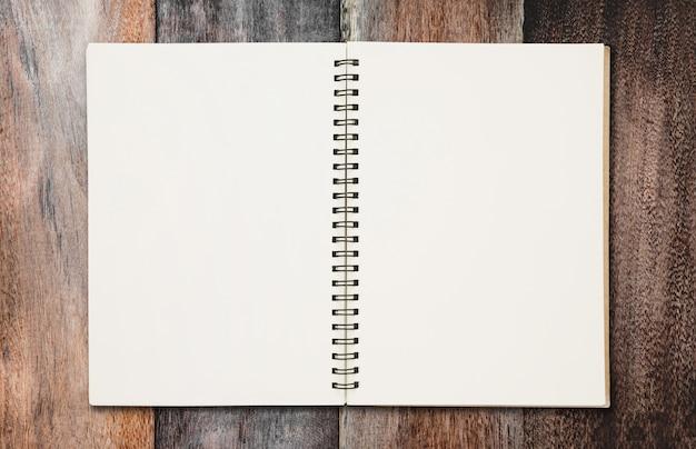 Cahier à reliure ouverte sur la texture du bois