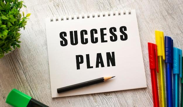 Un cahier sur un ressort avec le texte plan de réussite