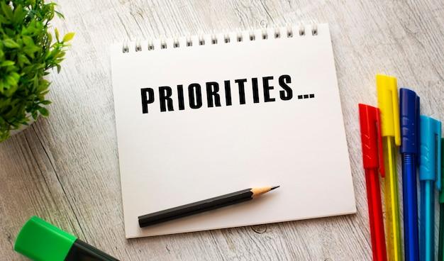 Un cahier sur un ressort avec le texte priorités sur une feuille blanche se trouve sur une table en bois