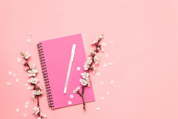 Cahier rose et un brin de fleurs