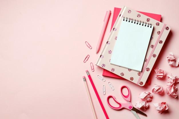 Cahier rose sur fond rose avec des fournitures scolaires roses. place pour le texte. vue de dessus.