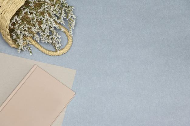 Cahier rose, panier de papier et de paille avec des fleurs sur fond gris