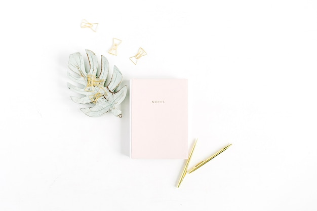 Cahier rose pastel pâle, stylo et clips dorés, décoration feuille de palmier monstera sur blanc