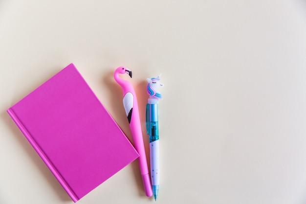 Cahier rose pour notes, stylos rigolotes licorne et flamants sur fond jaune pastel. lay plat. vue de dessus. espace de copie