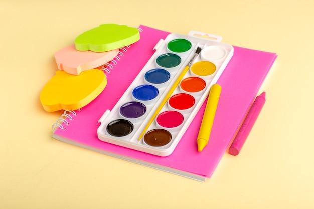 Cahier rose vue de face avec des peintures colorées sur une surface jaune clair