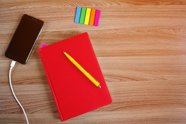 Cahier rouge fermé, téléphone sur fond de bois, vue du dessus