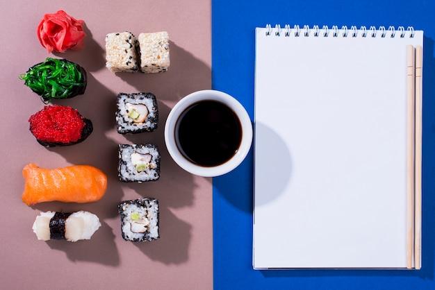 Cahier avec des rouleaux de sushi à côté