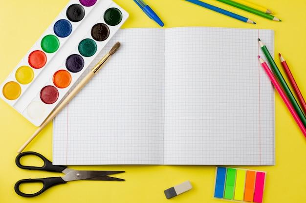 Le cahier se trouve avec des accessoires sur un fond jaune.