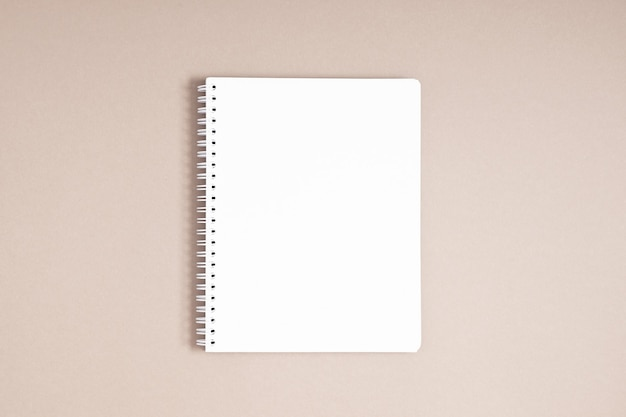 Cahier à spirale blanc élégant sur fond beige vue de dessus à plat
