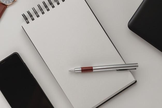 Cahier à spirale blanc ouvert avec une feuille vierge et beaucoup d'accessoires de bureau, une montre-bracelet, un téléphone portable, un étui à stylo et un ordinateur portable.