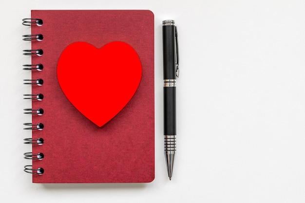 Cahier à spirale avec coeur sur la couverture et stylo