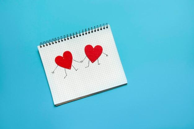 Cahier à spirale avec deux coeurs main dans la main