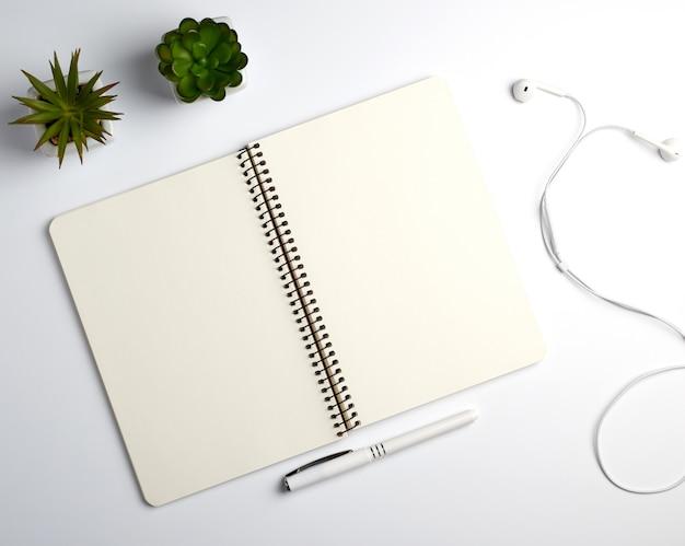 Cahier à spirale avec draps vides, stylo et plantes vertes