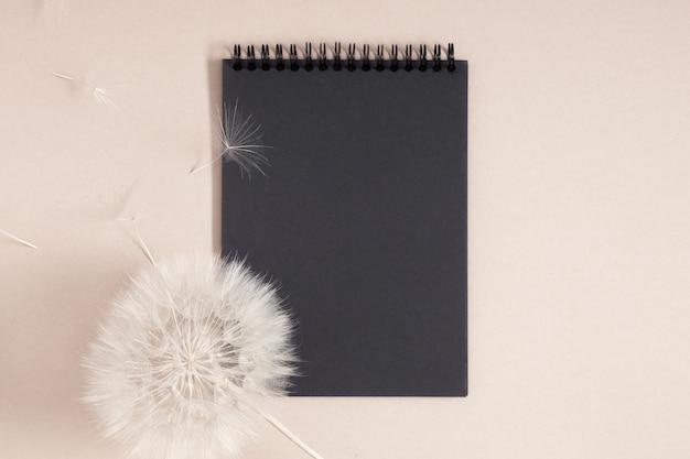 Cahier à spirale noir et plante sèche sur fond beige vue de dessus à plat