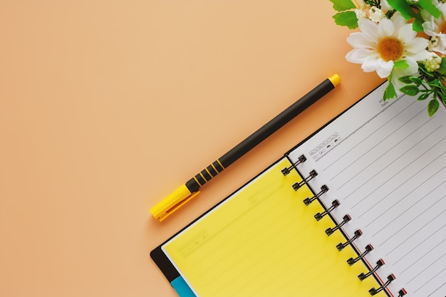 Cahier à spirale ouvert et un stylo avec des fleurs sur fond de couleur beige