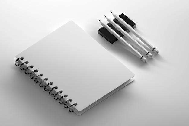 Cahier à spirale avec trois crayons de carbone sur une surface blanche