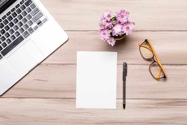 Cahier de stylo feuille de papier vide et fleurs sur la table