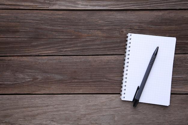 Cahier et stylo sur fond en bois gris