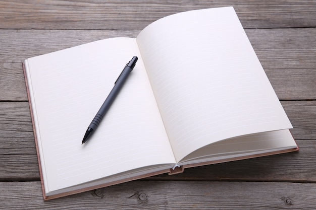 Cahier et stylo sur fond de bois gris