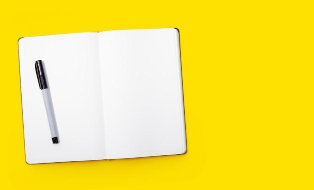 Cahier avec stylo sur fond jaune.