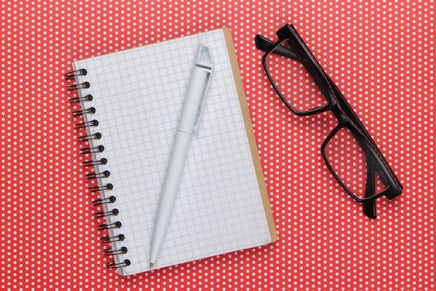 Cahier avec stylo et lunettes sur une nappe à pois.