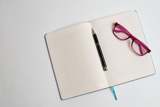 Cahier avec stylo noir et lunettes