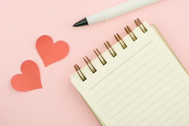 Cahier de stylo portant et jaune vierge sur fond rose.