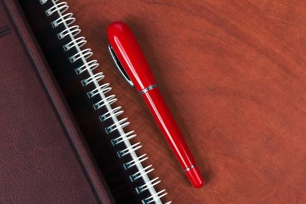 Le cahier et un stylo rouge allongé sur un bureau en bois