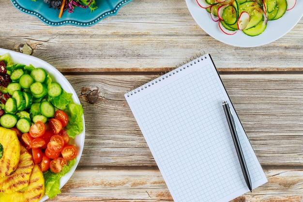 Cahier et stylo avec des salades saines sur table en bois
