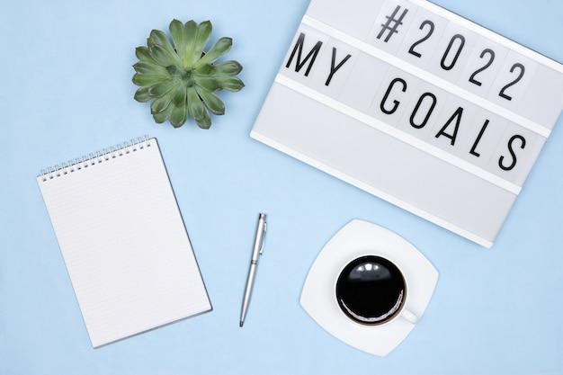 Cahier stylo tasse à café lightbox avec texte mes objectifs sur le bureau plans pour l'année à venir