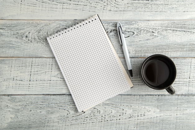 Cahier, stylo et tasse de thé ou de café sur bois blanc minable vintage, vue de dessus