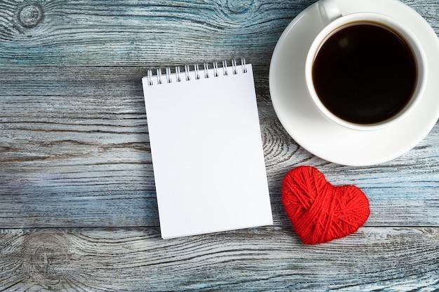 Cahier, tasse à café et coeur rouge sur fond en bois.
