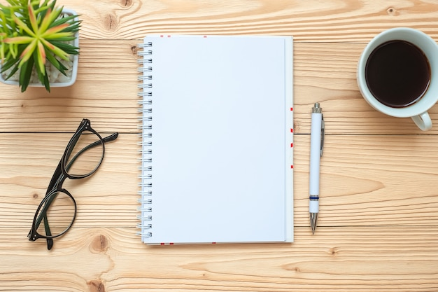 Cahier, tasse à café noire, stylo et lunettes sur la table