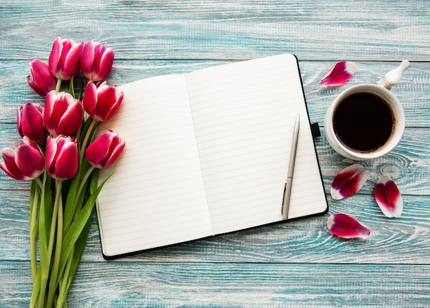 Cahier, tasse de café et tulipes roses