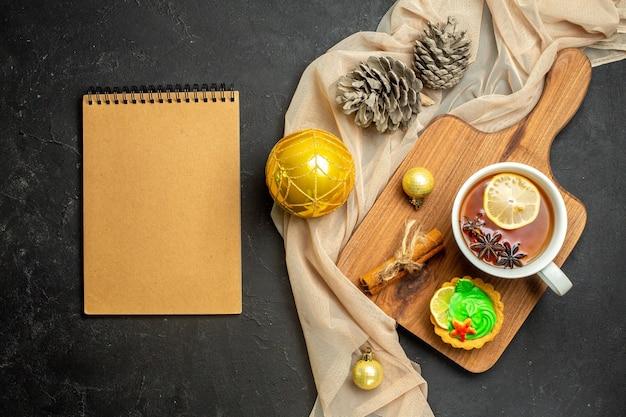 Cahier et une tasse de thé noir avec des accessoires de décoration de nouvel an au citron et à la cannelle sur une planche à découper en bois