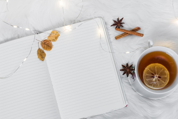 Cahier avec une tasse de thé sur un plaid blanc