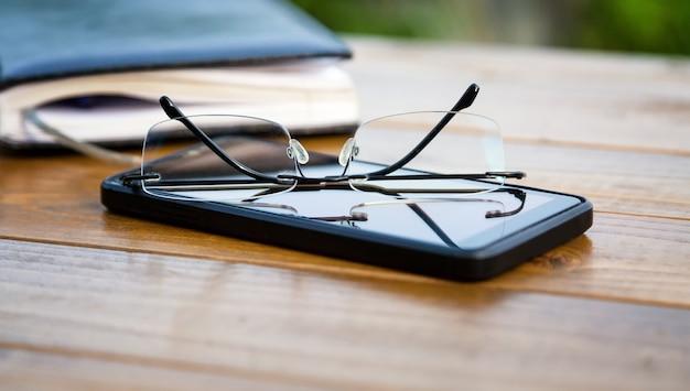 Cahier de téléphone de lunettes sans monture sur la table en gros plan
