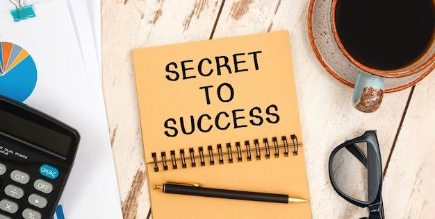 Cahier avec le texte secret to success sur la table de bureau, documents, calculatrice, lunettes et stylo