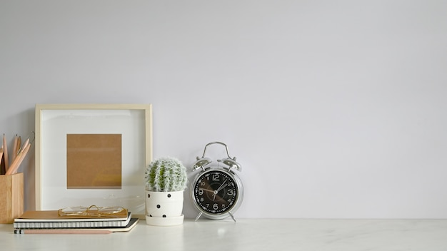 Cahier de travail, cadre photo, plante de cactus sur une table en marbre.