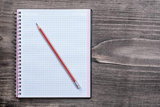 Cahier vérifié blanc avec un crayon sur le concept d'éducation de planche de bois brun pin
