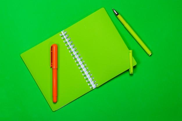 Cahier vert et deux stylos sur fond de couleur