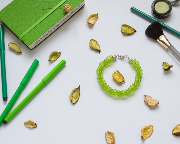 Cahier vert et stylos, cosmétiques sur fond blanc