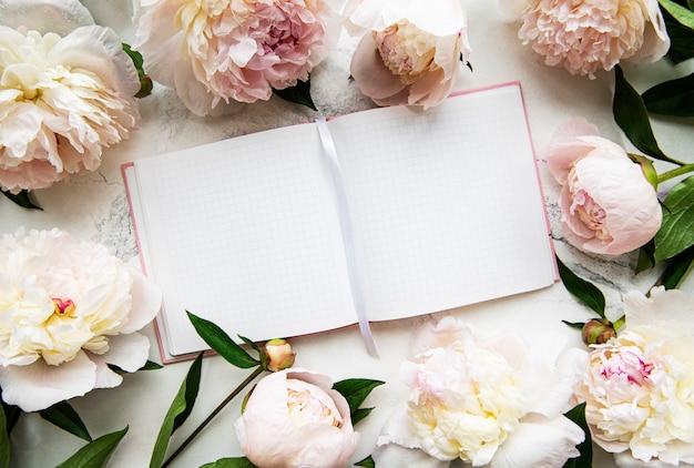 Cahier vide et fleurs de pivoine rose sur la surface de la pierre blanche, vue de dessus dans un style plat