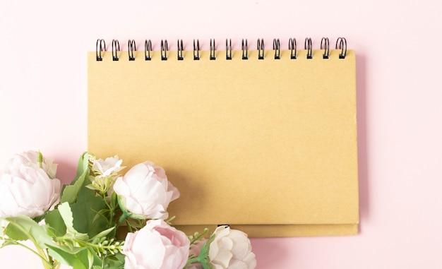 Cahier vide avec place pour le texte et les fleurs de pivoines sur une surface en bois blanche