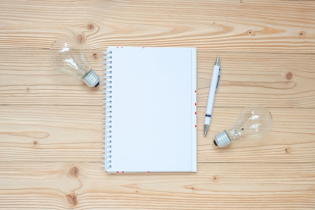 Cahier vierge avec ampoule et papier émietté sur une table en bois