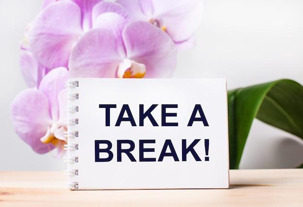 Cahier vierge blanc avec le texte prenez une pause sur la table sur fond d'orchidée rose clair.