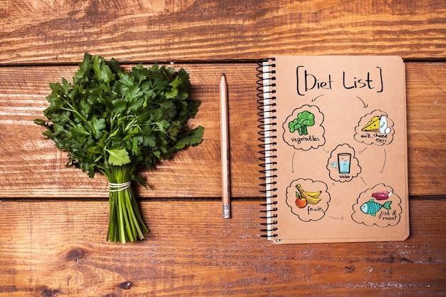 Cahier vierge et crayon avec un tas d'herbes sur planche de bois. notion de régime