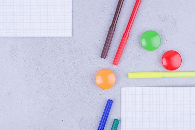 Un cahier vierge avec des crayons de couleur autour de la surface grise
