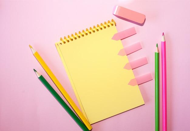 Cahier vierge avec des crayons de couleur sur fond pastel rose.